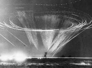 A long exposure shot of a C-130 circling and firing at a night target