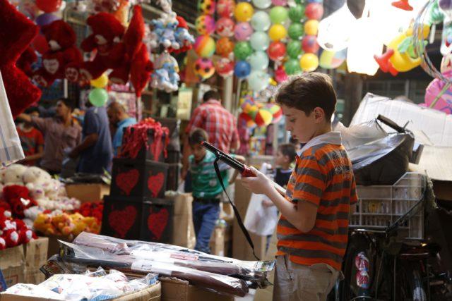 A child inspects a toy gun in Al-Asrouniyeh souk ahead of Eid al-Fitr celebrations in Damascus July 27, 2014. REUTERS/Omar Sanadiki (SYRIA - Tags: RELIGION SOCIETY)
