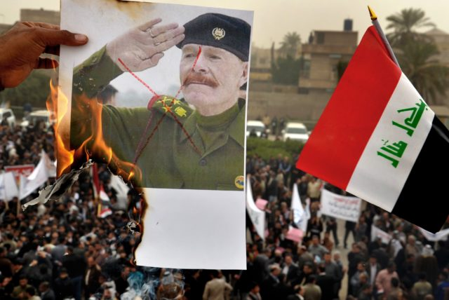 A protester sets fire to a poster of Izzat Ibrahim al-Douri, the highest ranking member of Saddam Hussein's ousted regime still at large, next to national flag as protesters chant pro-Iraqi Prime Minister Nouri al-Maliki slogans during a demonstration in Basra, Iraq's second-largest city, 340 miles (550 kilometers) southeast of Baghdad, Iraq, Tuesday, Jan 8, 2013. Demonstrators have taken to the streets in Iraq's second largest city to back the government of Prime Minister Nouri al-Maliki, which has weathered over two weeks of angry protests. (AP Photo/Nabil al-Jurani)