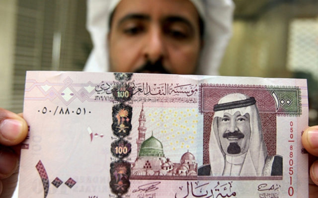 A Saudi banker displays the new one hund...Riyadh, SAUDI ARABIA: A Saudi banker displays the new one hundred riyal banknote bearing the portrait of Saudi King Abdullah bin Abdul Aziz al-Saud at a bank in Riyadh, 05 June 2007. The banknotes featuring the king are the fifth issue released by the Saudi Arabian Monetary Agency (SAMA). AFP PHOTO/HASSAN AMMAR (Photo credit should read HASSAN AMMAR/AFP/Getty Images)