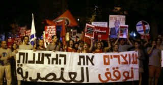 """Israeli Jews and Arabs hold a banner reading in Hebrew and Arabic """"Stopping the racism"""" as they march together in downtown Jerusalem on October 17, 2015"""