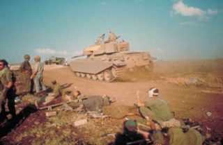Israeli tank driving past wounded soldiers during the Yom Kippur War (October 1973).